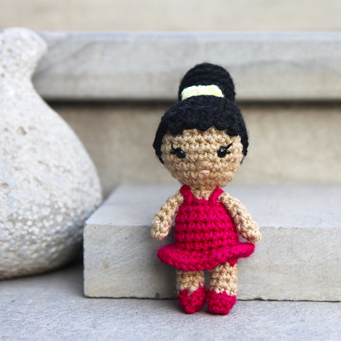 mini crochet ballerina doll with a pink dress, hair bun, and a yellow bow in her hair