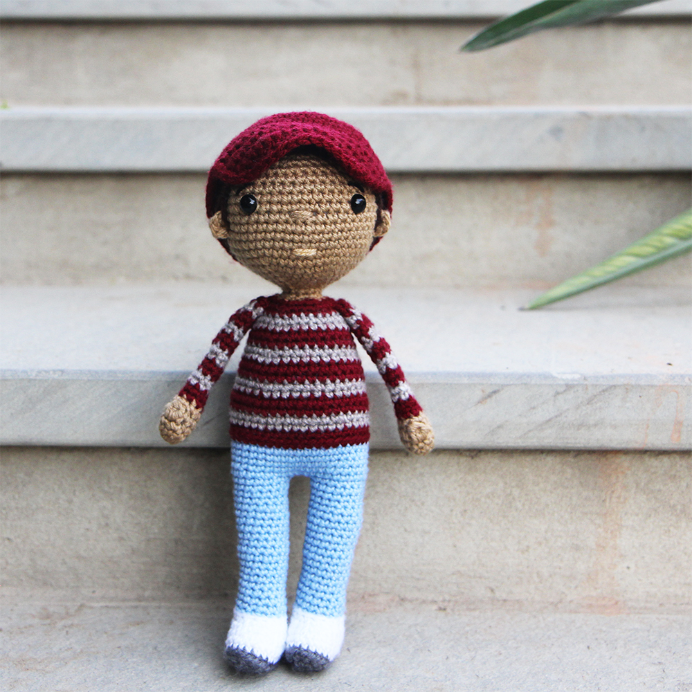 crochet boy doll with maroon and grey striped sweater and a maroon baseball cap
