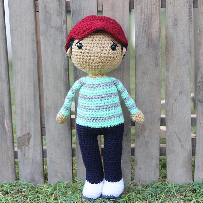 crochet boy doll with blue and grey striped shirt and maroon baseball cap