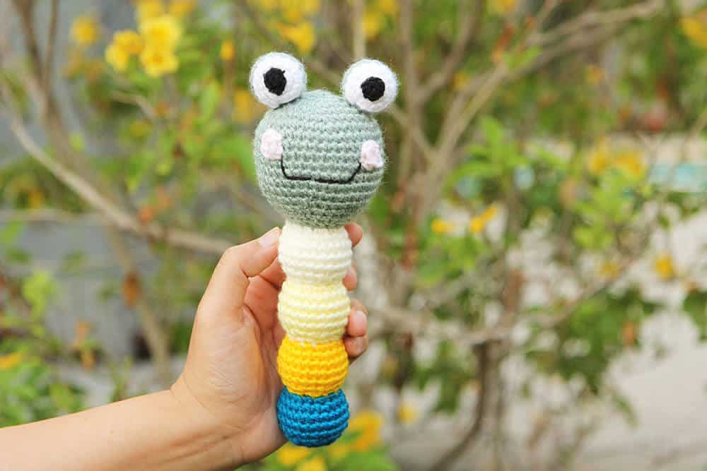 A crochet frog baby rattle in a hand
