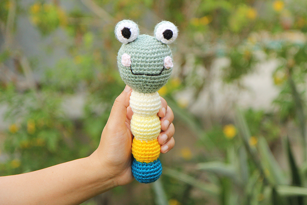 Crochet frog rattle with two bulging eyes and a smile with pink cheeks. The stem is made of four balls in blue, yellow, lemon yellow, and white.