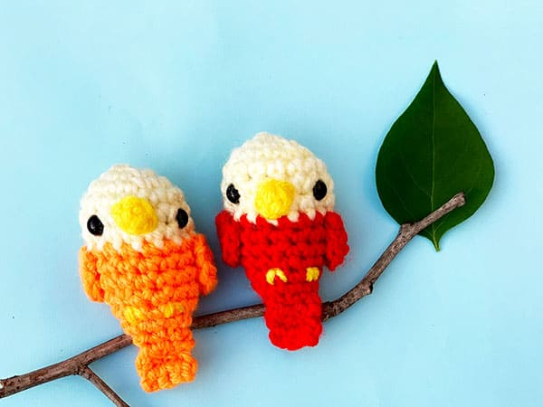 two small crochet birds sitting on a branch